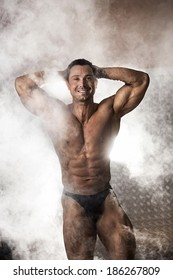 Portrait of male bodybuilder surrounded with smoke