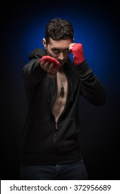 Portrait of a male boxer. Young sporty man on a dark background.