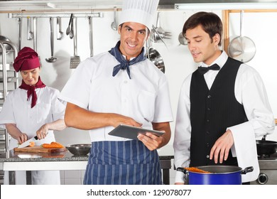 Portrait of male chef with waiter using digital tablet in commercial kitchen