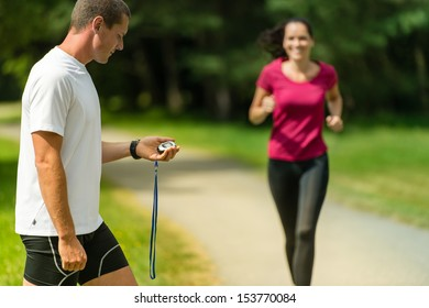 Portrait of male coach timing runner in a park