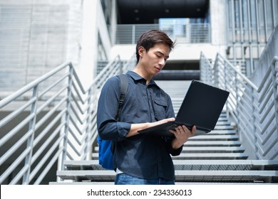 portrait of male college student use laptop at campus