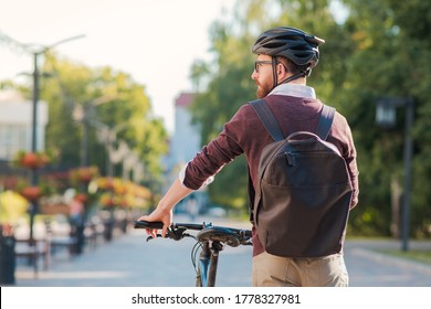 Portrait of a male commuter wearing bike helmet in a town. Safe cycling in city, bicycle commuting, active urban lifestyle image