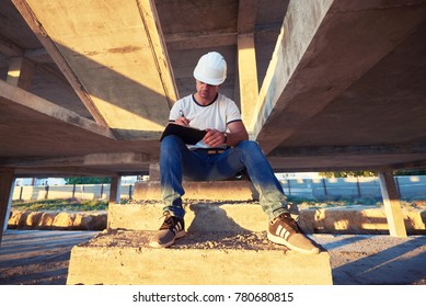Portrait of a male construction worker writing on clipboard young engineer writing on writing pad. Young construction engineer in white helmet writes in folder