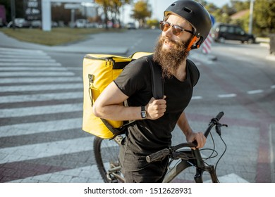 Portrait of a male courier walking with bicycle on the city steet, delivering food with yellow thermal backpack. Food delivery concept