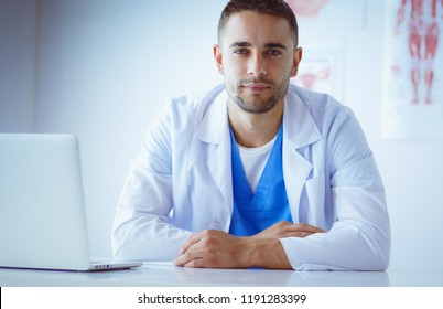 Portrait of a male doctor with laptop sitting at desk in medical office