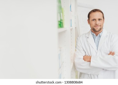 Portrait of a male doctor or pharmacist in white coat, standing with his arms crossed, next to wall shelfs with medicine. Half-length portrait with white copy space