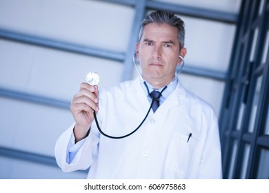 Portrait of male doctor showing stethoscope in hospital