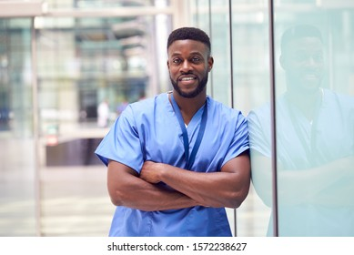 Portrait Of Male Doctor Wearing Scrubs Standing In Modern Hospital Building