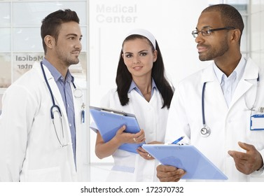 Portrait of male doctors and young nurse at medical center.