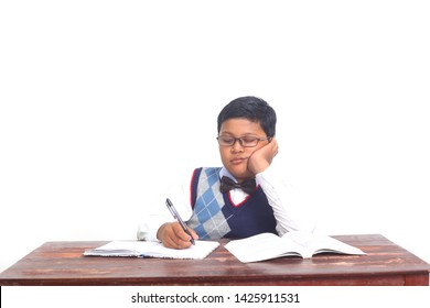 Portrait of male elementary student studying in the classroom and looks tired, isolated on white background