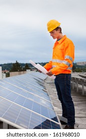 Portrait Of Male Engineer Holding Blueprint Standing In Front Of Solar Panel