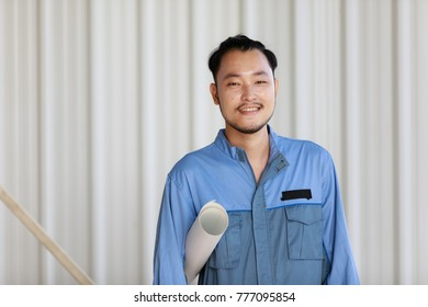 Portrait of male engineer with self-confidence and friendly manner, holding roll paper