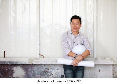 Portrait of male engineer with self-confidense and friendly manner, holding roll paper