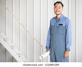 Portrait of male engineer wear coverall   with self-confidence and friendly manner, holding roll paper