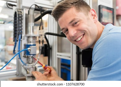 Portrait Of Male Engineer Working On Machine In Factory