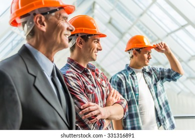 Portrait of male engineers builder in yellow helmet in the office center