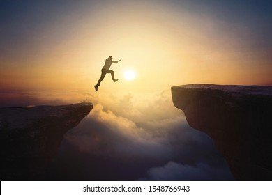 Portrait of male entrepreneur jumping through gap cliff at sunrise time