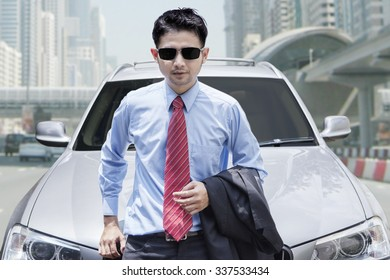 Portrait of male entrepreneur wearing sunglasses, standing in front of a new luxury car on the road