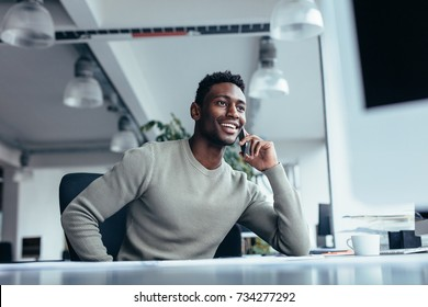 Portrait of male executive making phone call while sitting in office. Young businessman talking on mobile phone.