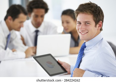 Portrait Of Male Executive Using Tablet Computer With Office Meeting In Background