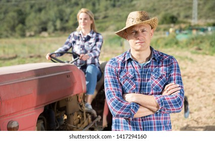 Portrait of male farmer on background with his wife tilling soil on farm tractor in vegetable garden