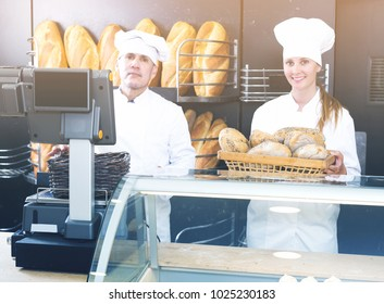 Portrait of male and female bakery employees offering delicious bread in bakery