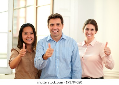 Portrait of male and female coworkers with ok sign smiling at you while standing on office background
