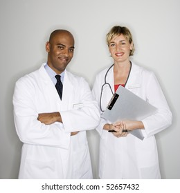 Portrait of male and female doctors standing smiling.