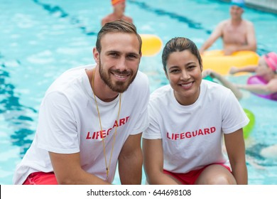 Portrait of male and female lifeguards crouching at poolside