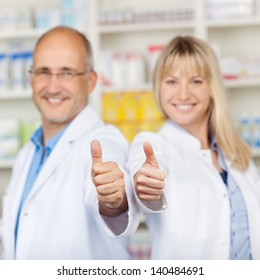 Portrait of male and female pharmacists showing thumbs up in pharmacy