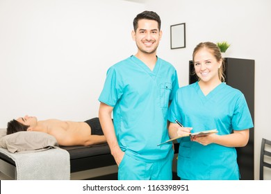 Portrait of male and female physiotherapists with clipboard standing in hospital
