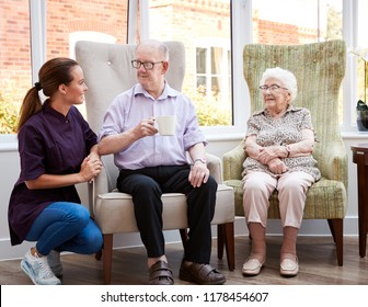 Portrait Of Male And Female Residents Sitting In Chairs In Lounge Of Retirement Home