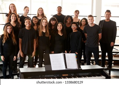 Portrait Of Male And Female Students Singing In Choir With Teacher At Performing Arts School