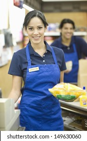 Portrait of male and female supermarket employees in blue apron