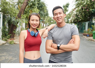 Portrait of male and female Vietnamese fitness trainers standing in the sreet and looking at camera