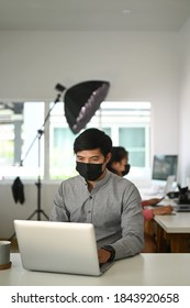 Portrait of male freelancer photographer with face mask is checking photos on a laptop while sitting at the table in workstation.