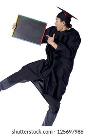 Portrait of male graduate jumping while pointing to the blackboard against a white background