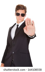 Portrait Of Male Guard In Suit Gesturing Stop Sign On White Background
