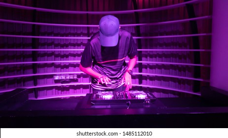 portrait of a male with hat Disc jockey or dj playing turn table, mixer, music on the club