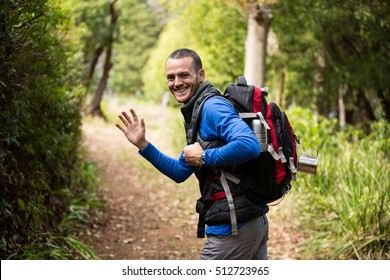 Portrait of male hiker waving hand while walking in forest