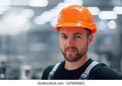 Portrait of male industrial worker indoors in factory. Young technician with orange hard hat.