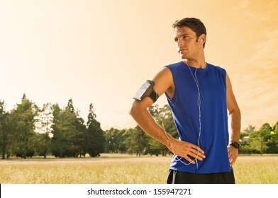 Portrait Of Male Jogger Standing In Field While Listening Music
