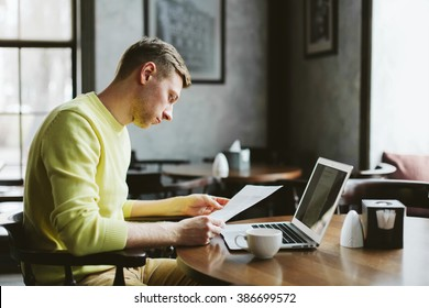 Portrait of the male journalist focused work on studying the material for a new article sitting at a table in a cafe