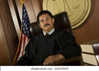 Portrait of male judge sitting on chair in courtroom