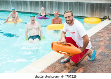 Portrait of male lifeguard crouching while swimmers swimming in pool