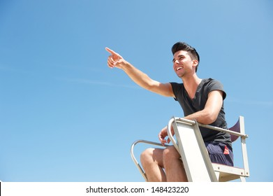 Portrait of a male lifeguard smiling and pointing into the distance on a summer day