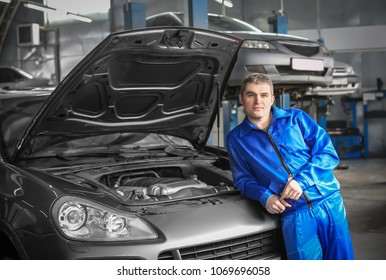 Portrait of male mechanic near car in service center