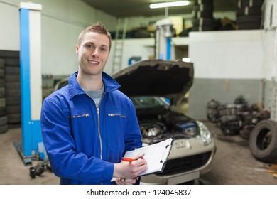 Portrait of male mechanic writing on clipboard in workshop