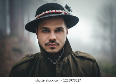 Portrait of male model with hat and beautiful eyes in deep forest at twilight. Woodsman in misty and foggy forest looking to the camera. Close up portrait of fashionable man.