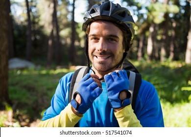 Portrait of male mountain biker wearing bicycle helmet in the forest on a sunny day